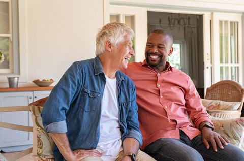 the image shows two men sitting on a chair laughing with each other