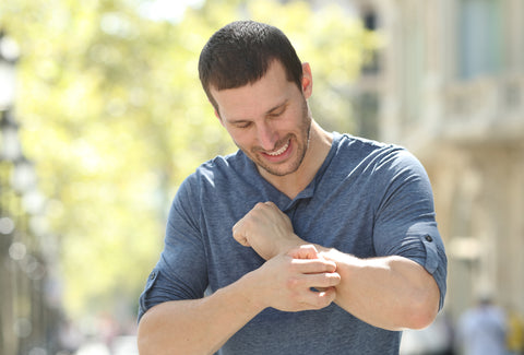 the image shows a man scratching his arm