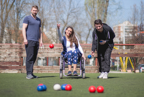 A photo showing a woman in a wheelchair in an outside setting throwing a red Boccia ball. Two men are either side of the woman
