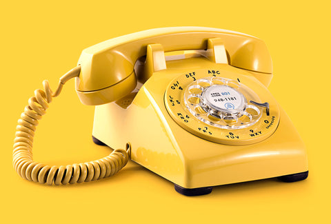 An old-fashioned dialling telephone in bright yellow. The background is also bright yellow
