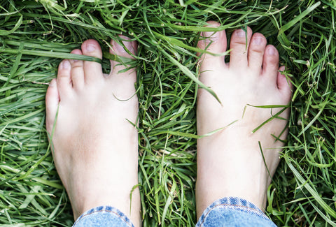 Two human feet standing on some long, green grass
