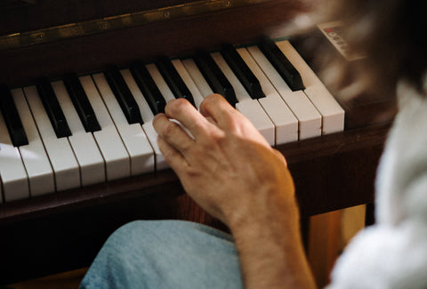 A picture of a left hand playing the piano
