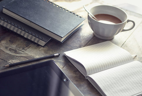 A picture of three notepads on a wooden table top. There is also a tablet, a cup of tea and a pencil also on the table