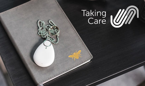 """A PPP TAKING CARE alarm is """"resting"""" on top of a grey book which is on a black table top. The TAKING CARE logo can be seen"""