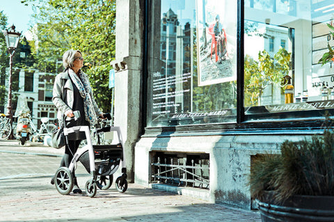 the image shows a woman window shopping with her rollz rollator