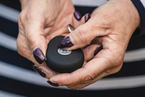 A close up of a woman pressing one of the button alarms