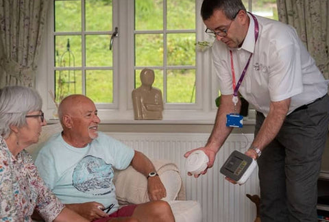 A man demonstrating some of the alarms to an elderly couple who are sitting on a sofa