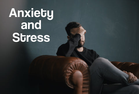 A man sitting on a sofa; his hand is raised to his head, although stressed. The words – Anxiety and Stress – can be seen