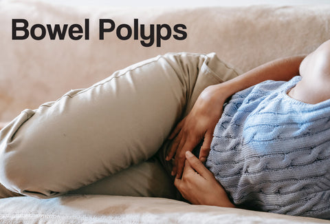 A person lying on a sofa clutching her stomach, as though in pain. The words – Bowel Polyps – can be seen