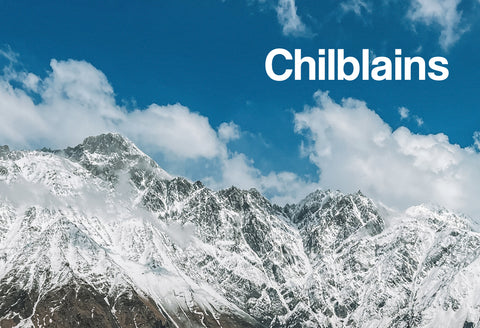 A snow covered mountain top with a cloudy and very blue sky. The word – Chilblains – can be seen