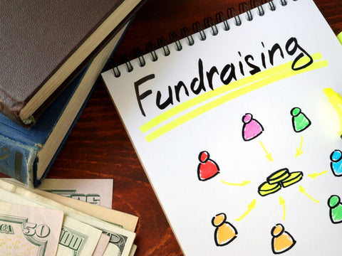 The image shows fundraising ideas on a notepad