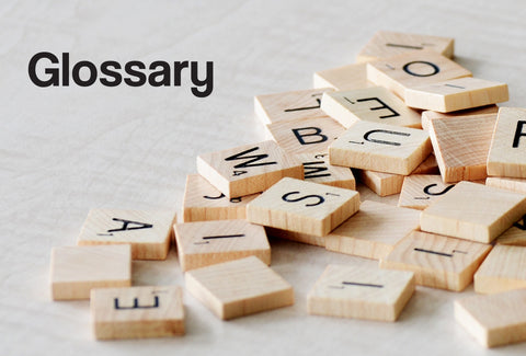 A jumbled pile of Scrabble letters all on top of one another. The word – Glossary– can also be seen