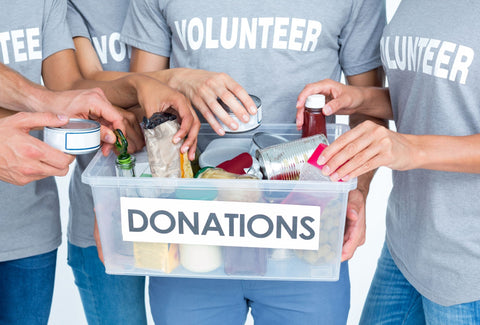 the image shows a group of volunteers with a donations charity box