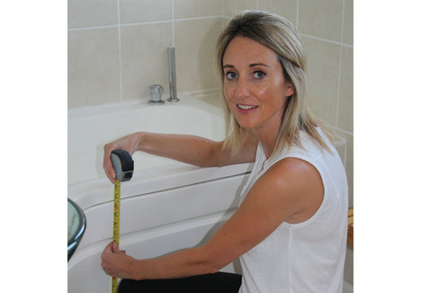 Kate measuring the height of a bath with a tape measure