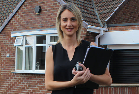 A picture of Kate Makin holding a clip board standing in front of a house