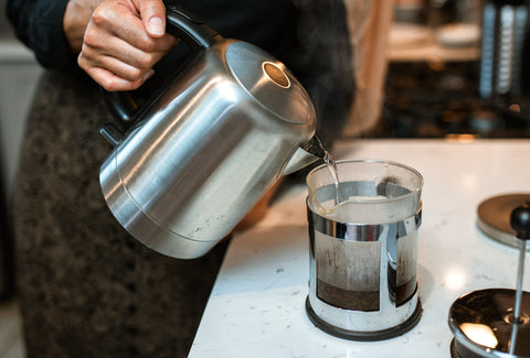 Someone pouring hot water into a cafetière