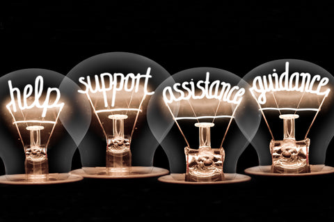 Four lightbulbs with their filaments replaced by four words – help, support, assistance and guidance
