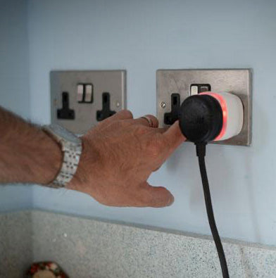 The Taking Care Safe Home Alert is plugged into the wall - its outer ring is lit up and a hand is pressing the button on the alarm