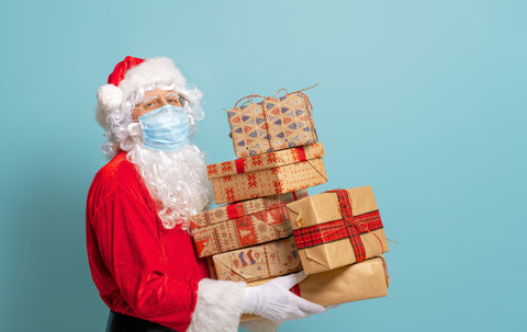 the image shows Santa Clause delivering presents and wearing a face mask