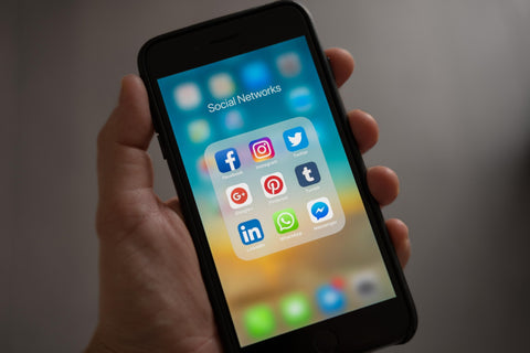 the image shows a mobile phone with social media icons on it