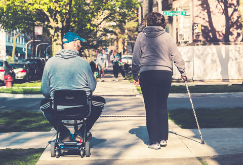 the image shows a man on a walker with a woman using a walking stick