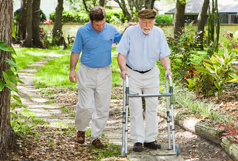 A man using a Zimmer frame on a country path, he is being helped by a friend