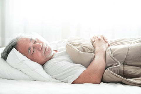 the image shows a man sleeping in bed on a comfy mattress