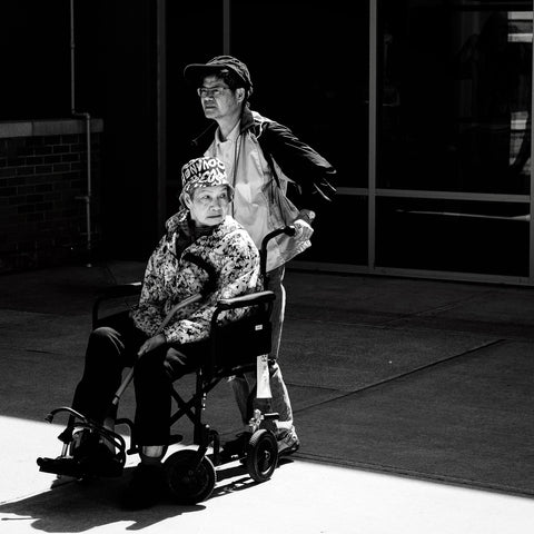 the image shows a person being pushed in a wheelchair