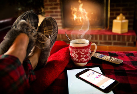 Person resting in slippers next to fireplace and hot drink