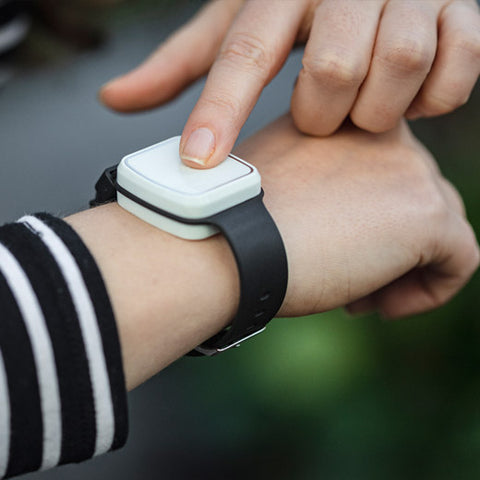 One of the Taking Care Alarms is shown on the wrist of a person. The person is pressing the alarm
