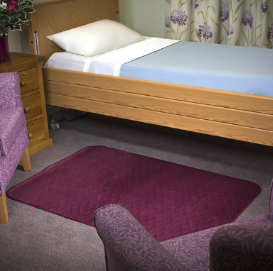 The image shows the Velour Floor Pad in maroon placed on a floor beside a single bed