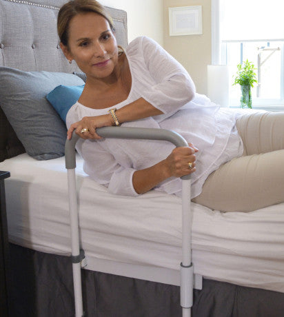 the image shows a woman using the smart-rail bed rail