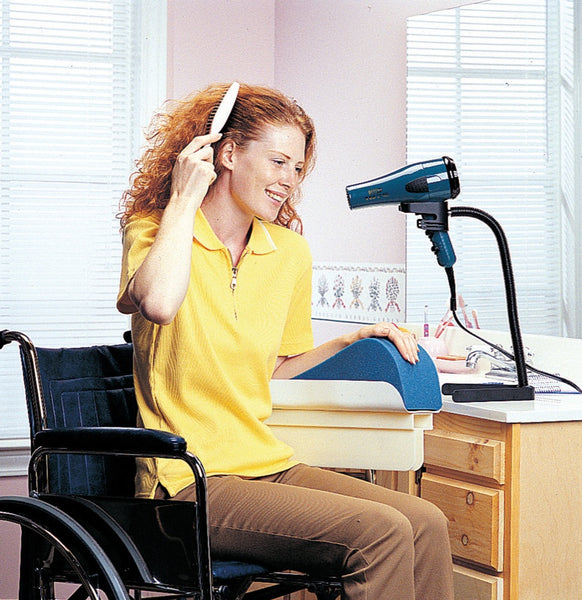 The image shows a young woman in a wheelchair, using the Hands Free Hair Dryer Stand to style her hair with one hand