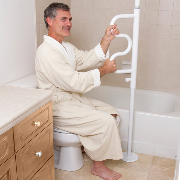 image shows a man in a dressing gown, using the Security Pole with Grab Bar to rise from a low toilet seat