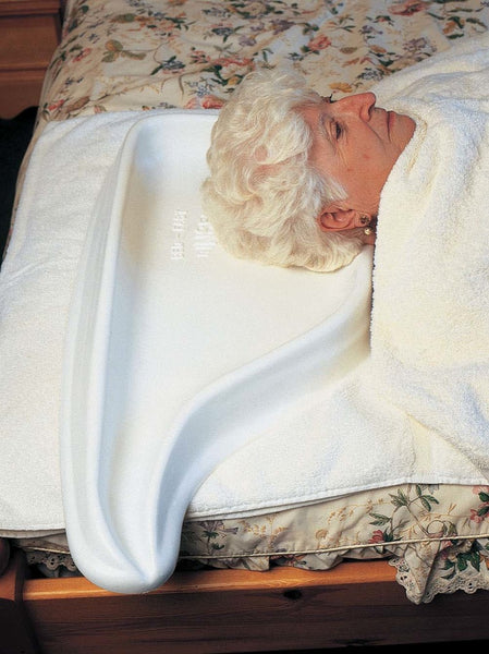 The image shows a woman with white hair lying in bed with the Hair Washing Tray for Bed Use in place beneath her head.