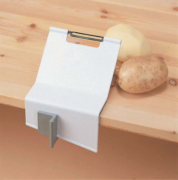 the image shows the homecraft gordon peeler and clamp fixed to a wooden surface with one peeled and one unpeeled potato beside it