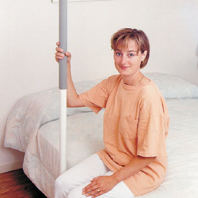 image shows the  floor mounted SuperPole Grab Rail fitted beside a bed and a young woman sitting on the bed holding on to the rail.