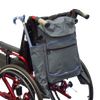 The image shows the crutch / stick holder bag for wheelchairs, attached to the back of a wheelchair with a folding walking stick / cane in one of the side pockets
