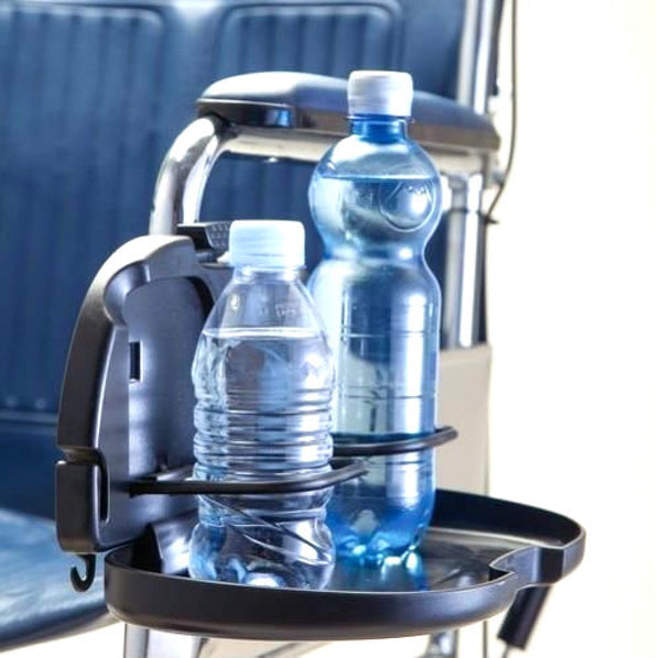 The image shows the double cup holder for wheelchairs fitted to the armrest of a wheelchair with two drinks bottles in the holder