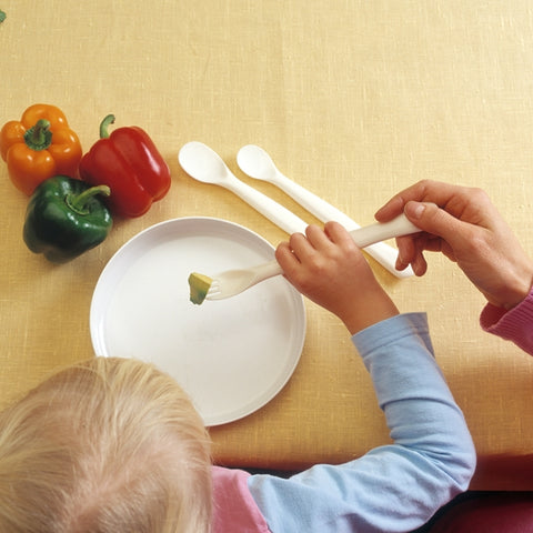 the image shows someone using an etac feeding spoon