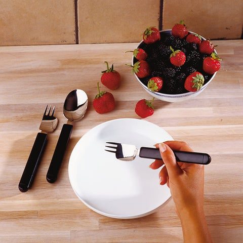 The image shows the Etav Light Combination Cutlery being used to eat some strawberries