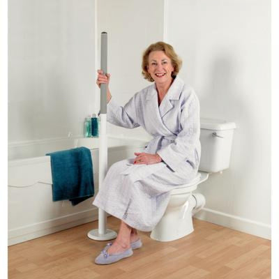 image shows a woman in a dressing gown and slippers sitting on a closed toilet lid, holding on to the Floor Mounted Advantage Grab Rail