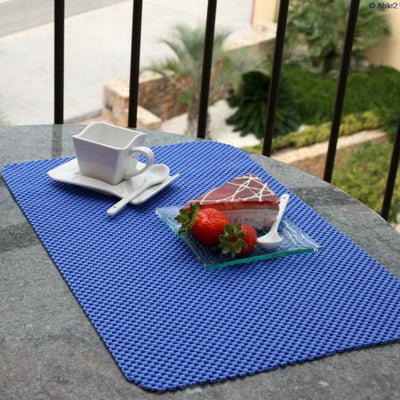 the image shows a plate with cake on it and a teap cup on a non-slip fabric tablemat