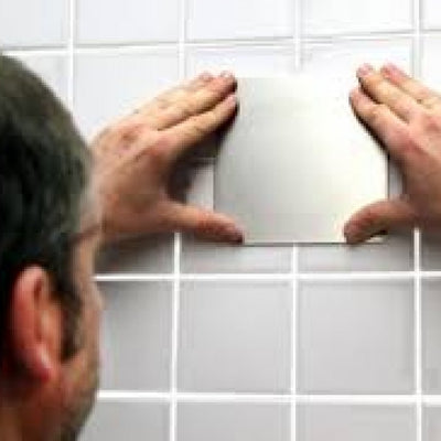 image shows a man fixing a Mobeli Cardan Steel Plate to a grey tiled wall