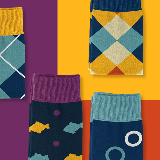 Colorful socks with multiple designs folded and arranged on a multicolor background - Goldie Socks