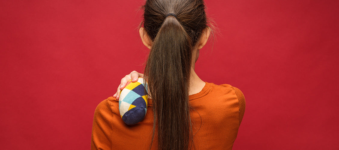 Woman with rice sock on shoulder to relieve pain - DIY Rice Sock