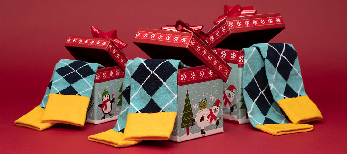 Men's, women's, and kids' matching socks in an argyle pattern hanging out of different sized Christmas boxes - Family Gift Ideas