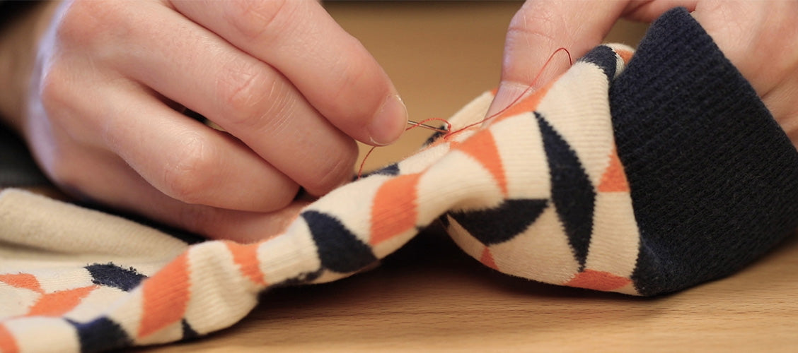 Threaded sewing needle being inserted into socks at the base of a snag