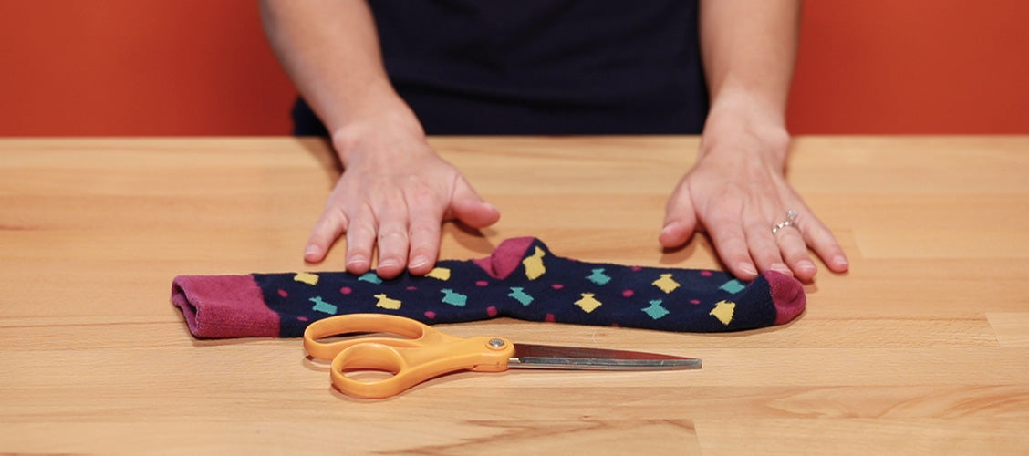 Sock laying on a craft table with scissors