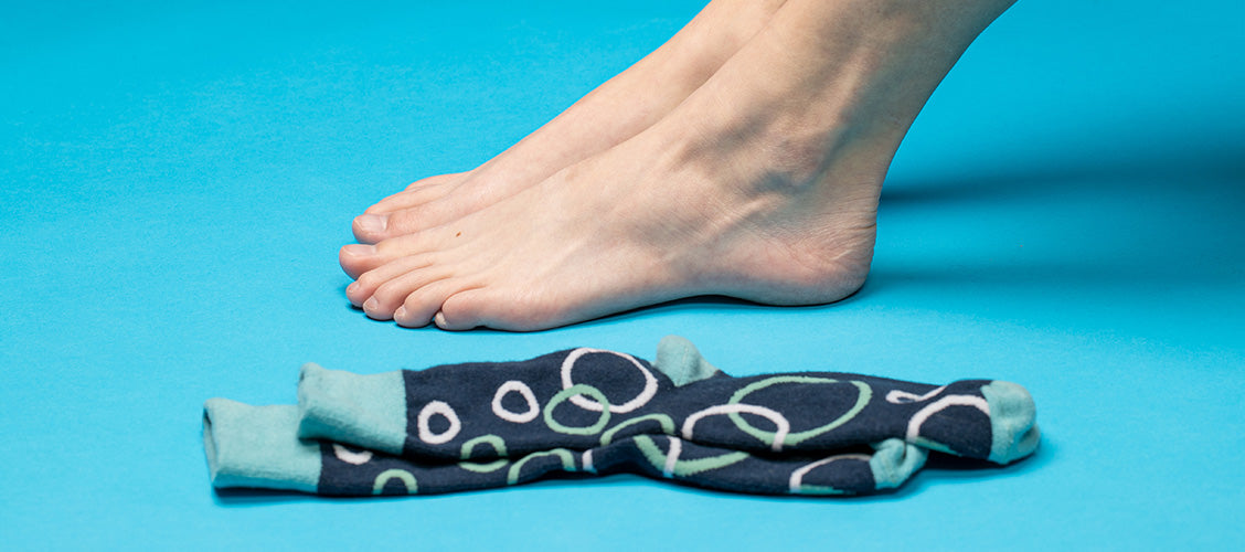 Woman sitting on floor with bare feet next to blue bubble socks - How to Put On Socks